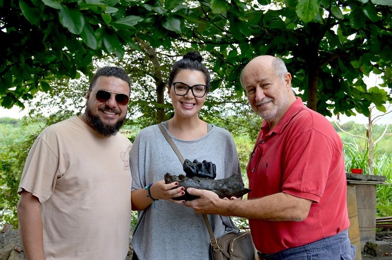 Da esq. para a dir.: Leonardo Avilla, Dimila Mothé e Gheny Krigfeld, primeira pessoa a encontrar fósseis na região, exibem parte de mandíbula de mastodonte (Foto: Arquivo do prof. Avilla)