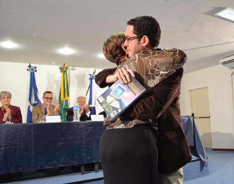 Eunice Pacitti entrega ao discente Arthur um livro do professor homenageado (Foto: Comso)
