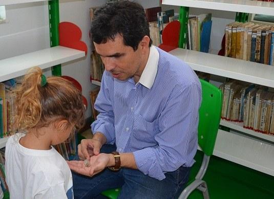 Ricardo Cardoso apresenta o tatuí para criança durante lançamento do livro (Foto: Comso)